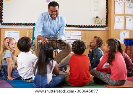 Elementary school kids sitting around teacher in a classroom - stock photo