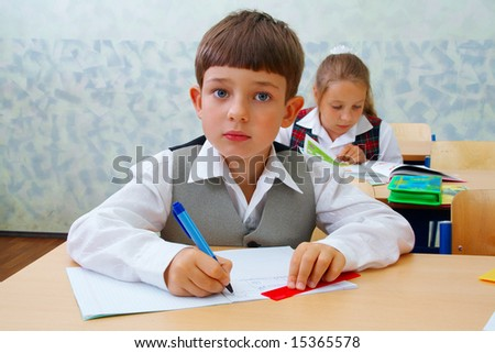 Elementary school. Pretty Schoolboy at the lesson. - stock photo