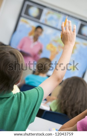 Elementary school pupil asking question in geography class - stock photo