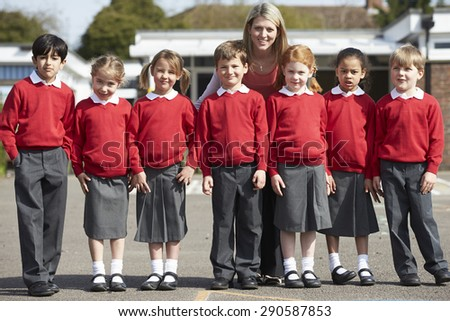 Elementary School Pupils With Teacher In Playground - stock photo