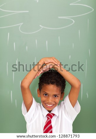 elementary school student in front of rain cloud drawn on chalkboard - stock photo