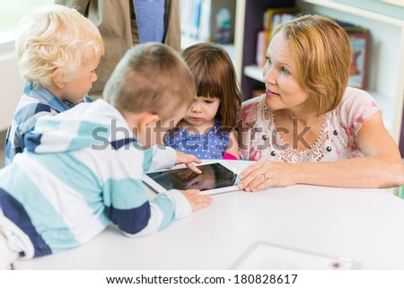 Elementary school teacher with students using digital tablet in library - stock photo