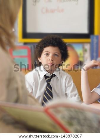 Elementary schoolboy listening to teacher reading in classroom - stock photo