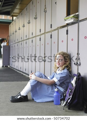 Elementary schoolgirl sitting on floor against school lockers, portrait - stock photo