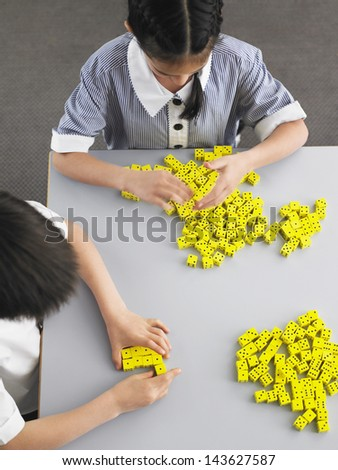 Elementary students playing with dice on desk in classroom - stock photo