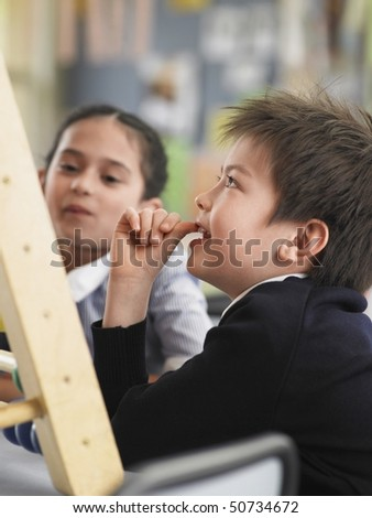 Elementary students sitting in classroom - stock photo
