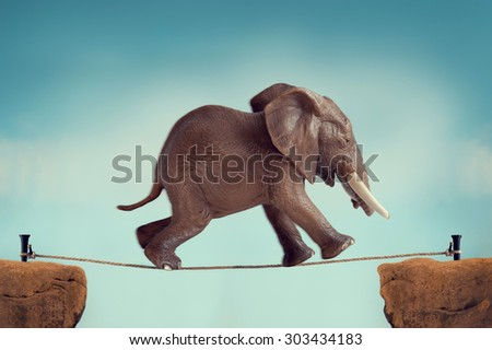 elephant running across a tightrope with motion blur and vintage filter - stock photo