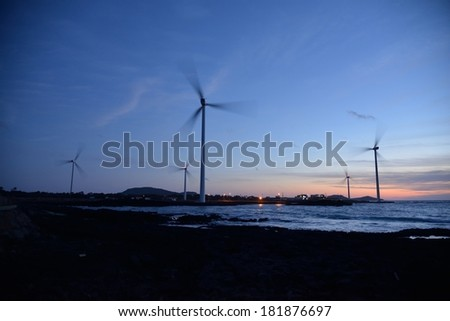 Eletric Power Generator Wind Turbine over a Cloudy Sky in Jeju Coast - stock photo