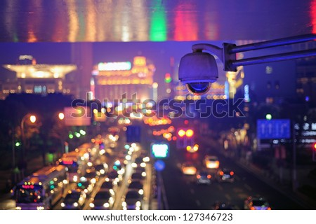 Elevated view at People's Square by night. Only security camera in focus. Colorful background is defocused Shanghai China - stock photo
