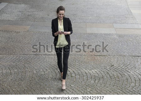Elevated view of a Businesswoman using her smart phone. Business woman standing outside in modern city. - stock photo