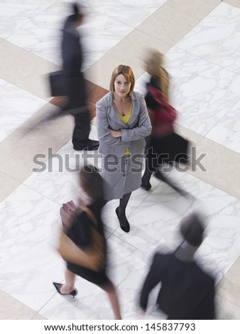 Elevated view of a confident businesswoman amongst blurred people walking - stock photo