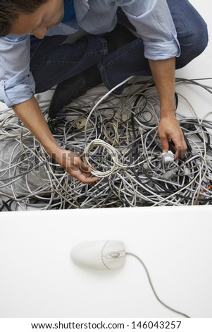 Elevated view of a cropped man working on tangled computer wires in office - stock photo