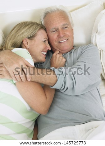 Elevated view of a happy middle aged couple embracing in bed - stock photo