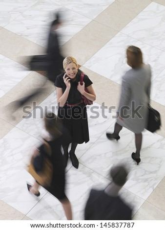 Elevated view of a smiling businesswoman using cellphone amongst blurred people walking - stock photo
