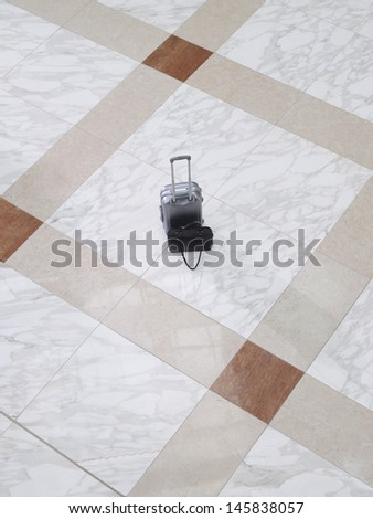 Elevated view of a suitcase and handbag on tiled floor - stock photo