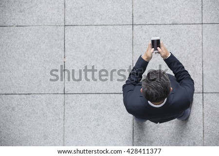 Elevated view of an Asian businessman using his Smart phone. - stock photo
