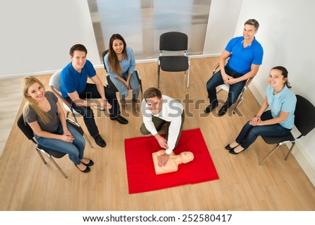 Elevated View Of First Aid Instructor Showing Resuscitation Technique On Dummy - stock photo
