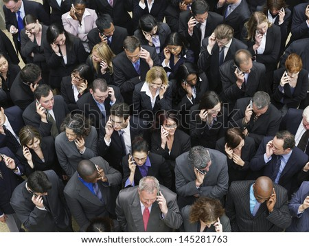 Elevated view of large group of business people using mobile phones  - stock photo