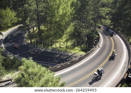 Elevated view of motorcycles driving on Iron Mountain Road, Black Hills, near Mount Rushmore National Memorial, South Dakota - stock photo