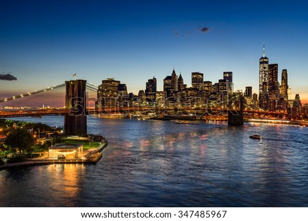 Elevated view of the Brooklyn Bridge and Lower Manhattan skyscrapers at dusk. The illuminated skyline of the Financial District reflects in the East River. New York City. - stock photo