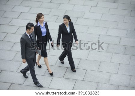Elevated view of three Chinese Business colleagues walking outdoors. Group of 3 Asian business men and women.  - stock photo