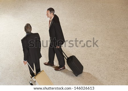 Elevated view of two businessmen pulling suitcases in airport lobby - stock photo