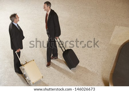 Elevated view of two businessmen with suitcases by luggage carousel in airport lobby - stock photo
