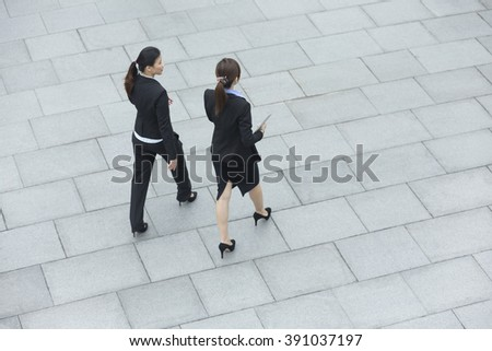 Elevated view of two Chinese business women walking outside modern office building. - stock photo