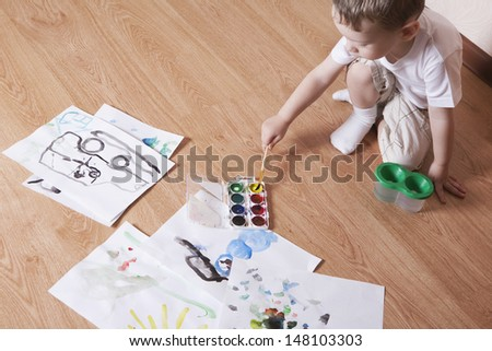 Elevated view of young boy painting with watercolors and paintbrush on laminated floor - stock photo