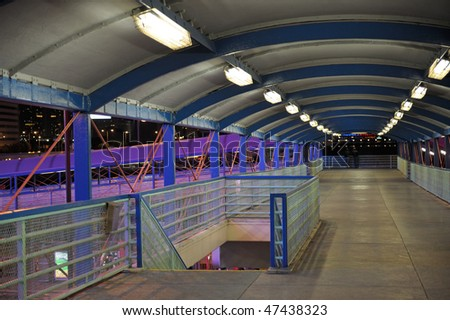 Elevated walkway illuminated by neon lights. Two persons in background - stock photo