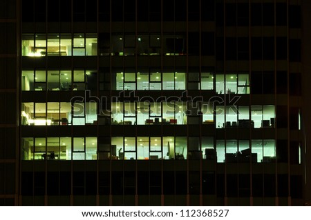 elevation of a modern office building at night with the lights t - stock photo