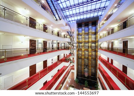 Elevators and floors with many doors in spacious hotel with glass roof. - stock photo