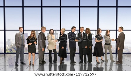 Eleven business professionals in a corporate environment meeting and conversing amongst themselves - stock photo
