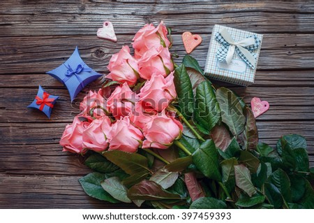 Eleven lovely stemmed pink roses and checkered pattern gift box over old wood background with copy space - stock photo