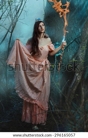 Elf girl in the fairy forest. She holds a staff in his hand. - stock photo