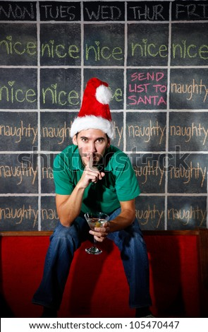 Elf man in front of naughty and nice December Christmas calendar with a martini in hand. - stock photo