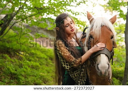 Elf woman in the forest with a horse - stock photo