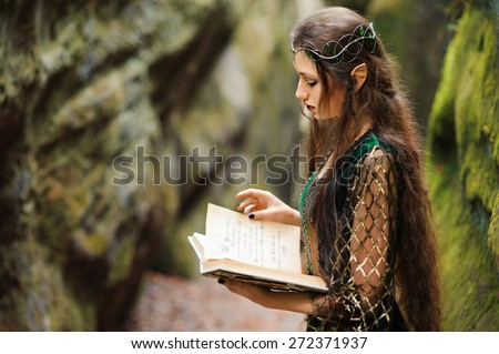 Elf woman reading a book in the mountains, magic tale - stock photo