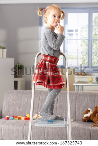 Elfish little girl standing on top of ladder, thinking impishly. - stock photo