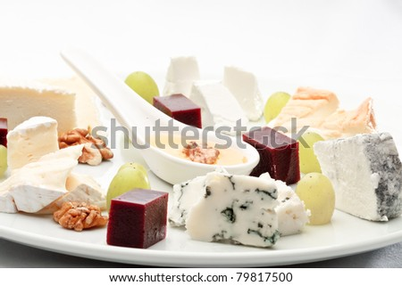 Elite French cheese assorted, decorated with fruit on a platter - stock photo