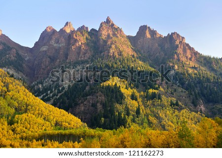 Elk Mountains of Colorado with golden and green trees during foliage - stock photo
