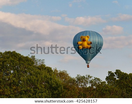 ELLICOTT CITY, MARYLAND - MAY 19, 2016: A blue hot air balloon featuring a teddy bear floats in the sky above Howard County Maryland during the annual Preakness Celebration Hot Air Balloon Festival. - stock photo