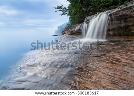 Elliot Falls, a small but beautiful waterfall on Miner's Beach at Michigan's Pictured Rocks National Lakeshore, spills over rock ledges and into Lake Superior after sundown. - stock photo