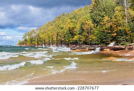 Elliot Falls (Miners Beach Falls) cascades into Lake Superior as waves break on the autumn coast of Pictured Rocks National Lakeshore in Michigan's Upper Peninsula. - stock photo