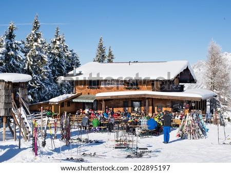 ELLMAU, AUSTRIA - JANUARY 29, 2014 : Unknown skiers are sitting at wood chalet bar for apres ski in Ellmau, Austria on January 29, 2014. - stock photo