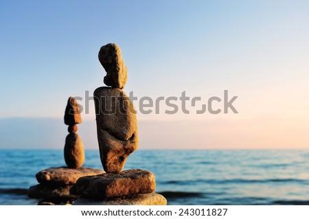 Elongated stones in balance on the seashore - stock photo