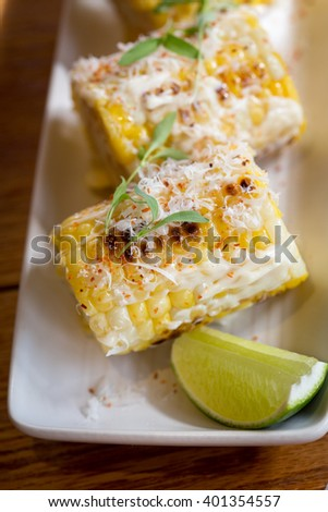 Elote or Mexican grilled corn on the cob served with cotija cheese and chili powder. - stock photo