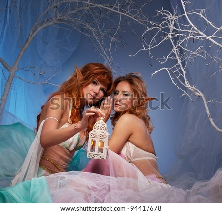Elves in magical winter forest with lantern. - stock photo
