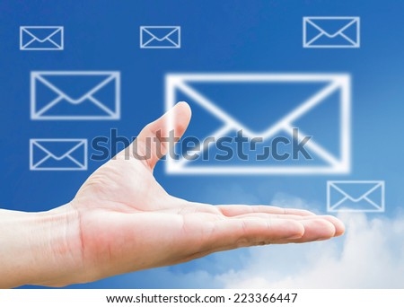Email icon on hand and mail symbol  icon clouds on blue sky  - stock photo