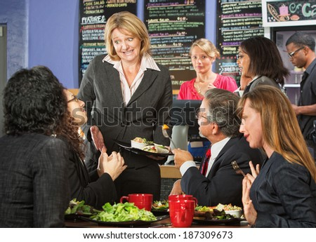 Embarrassed cafe manager with group of unsatisfied customers - stock photo